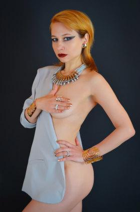 mulher de blazer maquiada cobrindo os seios com uma das mãos